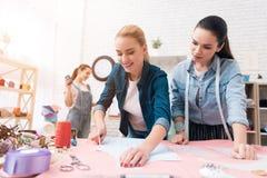 Tre kvinnor på plaggfabriken Ett av dem gör utklipp för ny klänning royaltyfria bilder