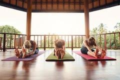 Tre kvinnor som öva paschimottanasana, poserar på yogagrupp Royaltyfria Foton