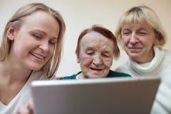 Tre kvinnor som använder en smart minnestavla Arkivfoto