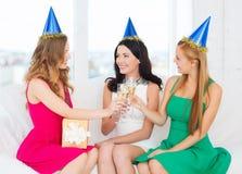 Tre kvinnor som bär hattar med champagneexponeringsglas Royaltyfri Fotografi