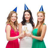 Tre kvinnor som bär hattar med champagneexponeringsglas Arkivbild
