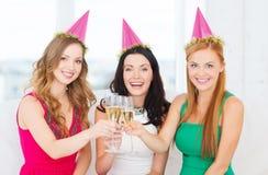 Tre kvinnor som bär hattar med champagneexponeringsglas Royaltyfri Bild
