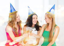 Tre kvinnor som bär hattar med champagneexponeringsglas Royaltyfria Bilder
