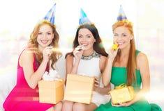 Tre kvinnor som bär hattar med gåvor som blåser horn Royaltyfri Fotografi