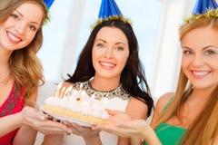Tre kvinnor som bär hattar som rymmer kakan med stearinljus Royaltyfri Foto