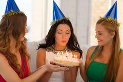 Tre kvinnor som bär hattar som rymmer kakan med stearinljus Royaltyfria Foton