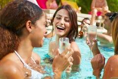 Tre kvinnor som har partiet i simbassängen som dricker Champagne Royaltyfri Fotografi