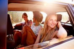 Tre kvinnor som sitter i bakre Seat av bilen på vägtur Arkivbild