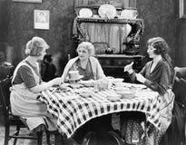 Tre kvinnor som sitter på det äta middag tabellsamtalet (alla visade personer inte är längre uppehälle, och inget gods finns Leve Royaltyfria Foton