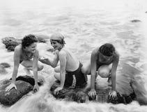 Tre kvinnor som spelar i vatten på stranden (alla visade personer inte är längre uppehälle, och inget gods finns Leverantörgarant royaltyfria foton