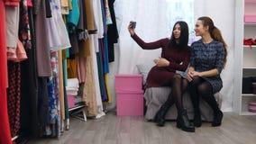 Tre kvinnor som tar en selfie i nya klänningar, medan shoppa i ett klädlager lager videofilmer