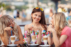 Tre kvinnor som tycker om koppen kaffe i kafé Arkivfoton