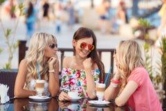 Tre kvinnor som tycker om koppen kaffe i kafé Royaltyfri Fotografi