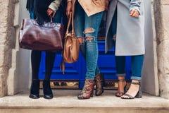 Tre kvinnor som utomhus bär stilfulla skor och tillbehör Höstmodebegrepp Damer som rymmer kvinnliga handväskor royaltyfri bild