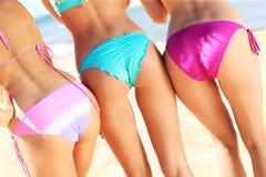 Tre kvinnor som visar deras baksida i bikini Arkivfoton
