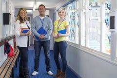Tre lärare i skolakorridor royaltyfri fotografi