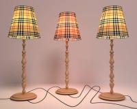 Tre lampade di pavimento sulle gambe di legno su un fondo leggero fotografia stock libera da diritti
