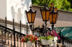 Tre lampade di via arancio contro lo sfondo delle pareti e della scala forgiata Fotografia Stock