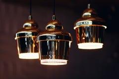 Tre lampor med guld- skugga som hänger från taket royaltyfri foto