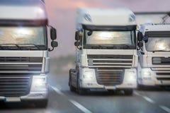 Tre lastbilar som rusar på en huvudväg Royaltyfri Fotografi