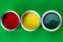 Tre latte aperte di pittura su un fondo verde fotografie stock libere da diritti