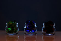 Tre latte delle pillole, pillole variopinte in banche, vetro Fotografia Stock
