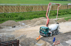 Tre lavoratori e camion concreto di trasporto con la pompa per calcestruzzo pronto per usare Questa attività è collegata con il P Fotografia Stock Libera da Diritti