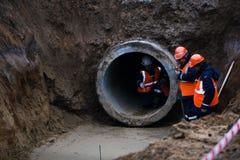 Tre lavoratori installano le grondaie concrete dal lato della strada, centrali elettriche Pagina che solleva il tubo concreto di  immagine stock