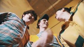 Tre lavoratori sporchi che guardano giù nella macchina fotografica che capisce, risata degli strats archivi video