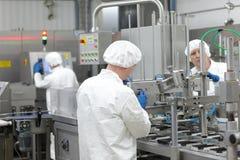 Tre lavoratori in uniformi alla linea di produzione in pianta Fotografia Stock Libera da Diritti