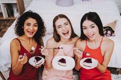 Tre le flickor med styckkakan i platta royaltyfria foton