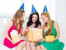 Tre le kvinnor i blåa hattar med gåvaaskar Royaltyfria Bilder