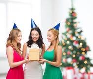 Tre le kvinnor i blåa hattar med gåvaasken Arkivfoton