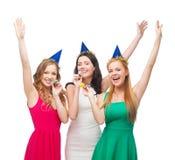 Tre le kvinnor i hattar som blåser favörhorn Arkivfoton