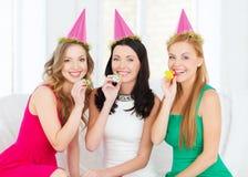 Tre le kvinnor i hattar som blåser favörhorn Fotografering för Bildbyråer