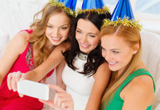 Tre le kvinnor i hattar som har gyckel med kameran Royaltyfri Bild