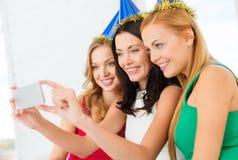 Tre le kvinnor i hattar som har gyckel med kameran Royaltyfri Fotografi
