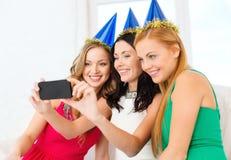 Tre le kvinnor i hattar som har gyckel med kameran Royaltyfria Bilder