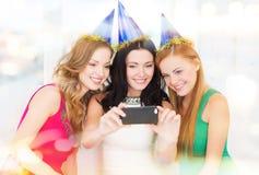Tre le kvinnor i hattar som har gyckel med kameran Arkivfoton