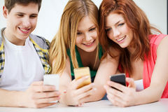 Tre le studenter med smartphonen på skolan Royaltyfri Fotografi