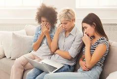 Tre ledsna kvinnor som hemma använder bärbara datorn royaltyfria foton