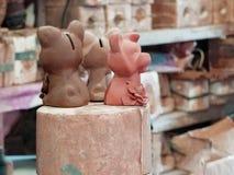 Tre lerastatyetter av hundkapplöpning handcrafted i arbetsplatsen arkivbild