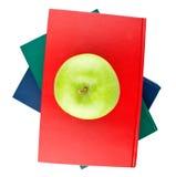 Tre libri di colore e vista verde della mela dalla parte superiore Immagini Stock