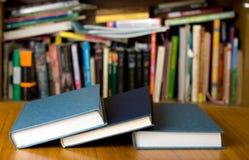 Tre libri sullo scrittorio di legno davanti allo scaffale per libri Immagini Stock