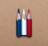 Tre lilla använda kulöra blyertspennor Royaltyfri Foto