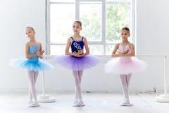 Tre lilla balettflickor, i ballerinakjol och att posera tillsammans Royaltyfri Foto