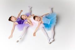Tre lilla balettflickor i ballerinakjolen som tillsammans ligger och poserar Arkivfoton