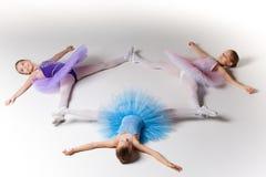 Tre lilla balettflickor i ballerinakjolen som tillsammans ligger och poserar Royaltyfri Bild