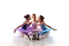 Tre lilla balettflickor som sitter i ballerinakjol och tillsammans poserar Arkivfoton