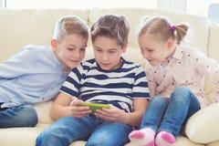Tre lilla barn som spelar med minnestavlaPC royaltyfria bilder